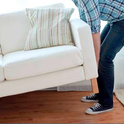 Картинка человек двигает диван перед обработкой от насекомых